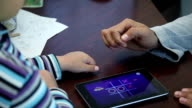 A man and a boy are playing on a tablet