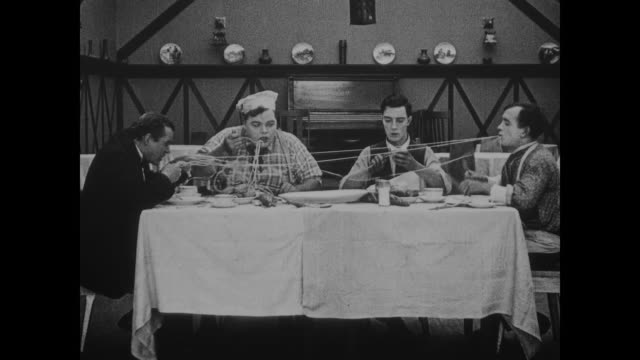 Buster Keaton and a knitting Fatty Arbuckle watch as two kitchen staff play tug of war with pasta, before cutting it to enjoy the rebound