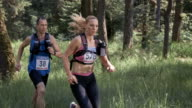 SLO MO DS A man and a woman running a trail marathon through the forest