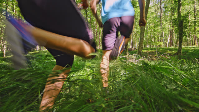 SLO MO Man and a woman running at cross-country through the forest
