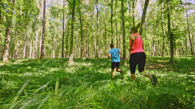 SLO MO Man and a woman running through the forest covered with fern