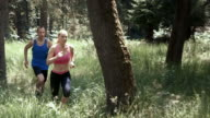 SLO MO DS Man and a woman running through the forest