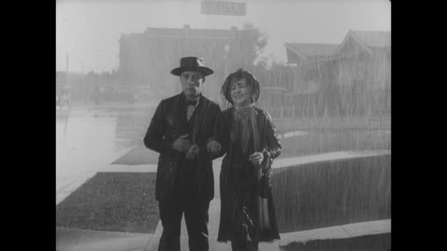 Buster Keaton and his mother (played by Florence Turner) walk slowly through a downpour