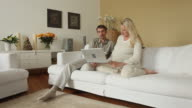WS DS Man and pregnant woman sitting on couch using laptop / Potsdam, Brandenburg, Germany