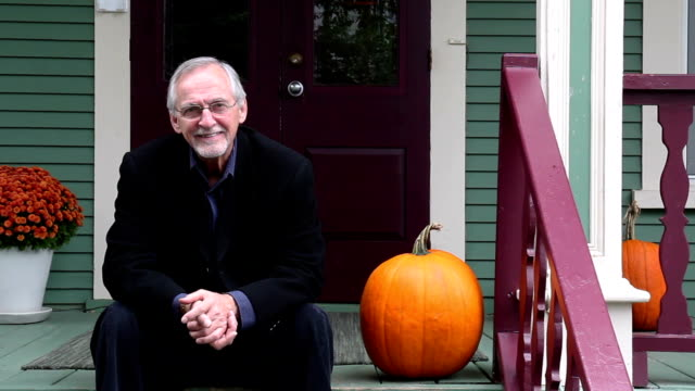 Man and pumpkin sitting on a country porch smiling