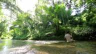 Mann und Spielen im Wald und stream