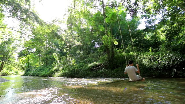 Man and swing in forest and stream