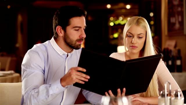 Man and woman at restaurant reading menu