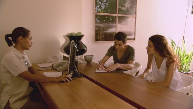MS Man and woman checking in at hotel reception / Hua Hin, Thailand
