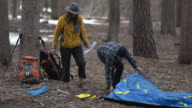 Man and woman couple setting up tent. Man struggles but refuses help from woman.