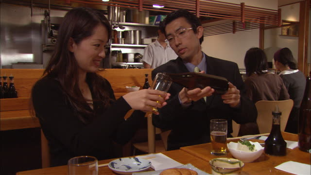MS, Man and woman drinking beer in Japanese restaurant