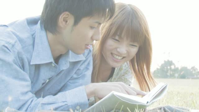 Man and woman enjoying reading lying on green