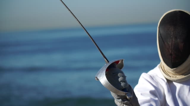 A man and woman fencing on the beach. - Slow Motion