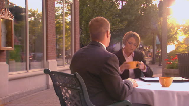 Man and woman having outdoor business meeting over coffee