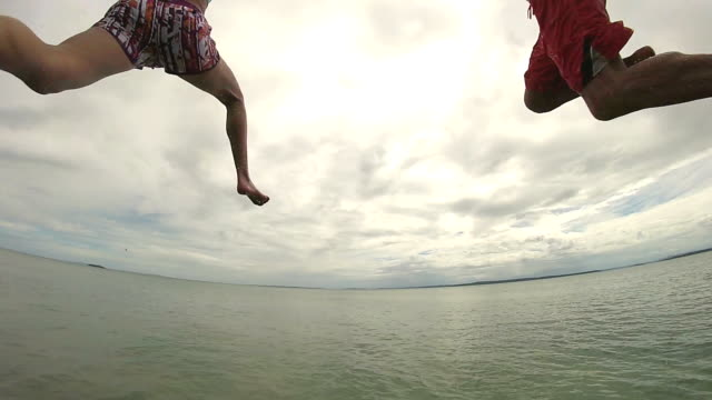 POV of man and woman holding hands jumping off end dock away from camera into tropical ocean.
