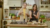 DS Man and woman hosting a cooking show trying a spread they made