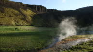Man and woman in a green field looking at a hot spring in Iceland