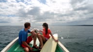 POV of man and woman in bow of boat holding surf board on sunny tropical ocean.