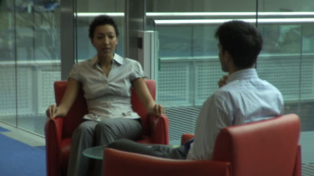 Man and woman in office conversation; UK