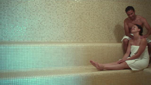 WS PAN Man and woman in sauna relaxing, man giving woman massage / Bellevue, Washington, USA