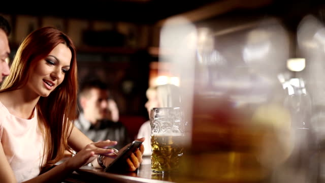 Man and woman in the Pub using tablet II