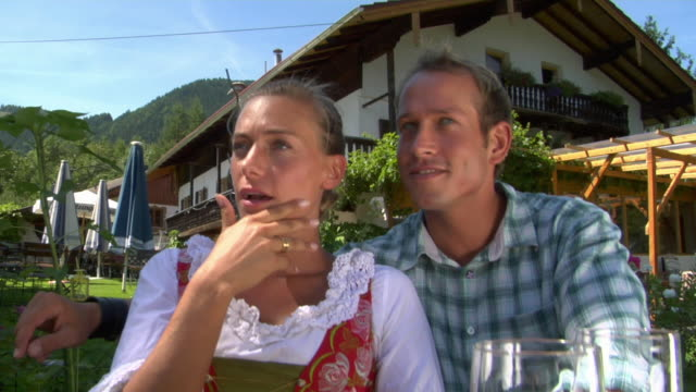 CU Man and woman in traditional dirndl dress talking in Bavarian landscape, Bavaria, Germany