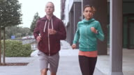SLO MO TS Man and woman jogging in the city