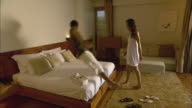 WS Man and woman jumping onto bed in resort hotel room / Hua Hin, Thailand