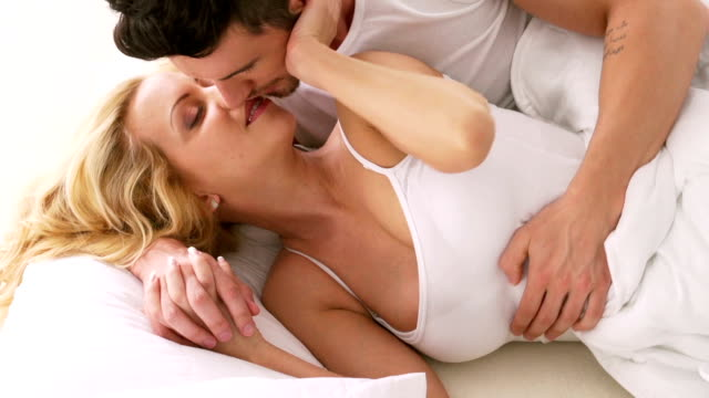 Man and woman kissing in bed, waking up
