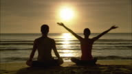 WS Man and woman meditating, sitting in yoga lotus pose, and woman stretching on beach at sunrise / Hua Hin, Thailand