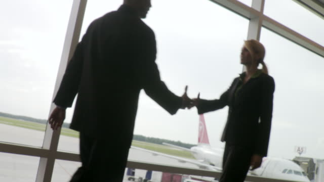 MS Man and woman meet and shake hand on airport  / Jacksonville, FL, United States