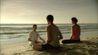 WS DS Man and woman on beach with meditation instructor, Hua Hin, Prachuap Khiri Khan, Thailand