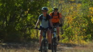 man and woman on mountain bikes