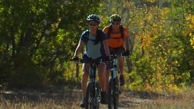 man and woman on mountain bikes
