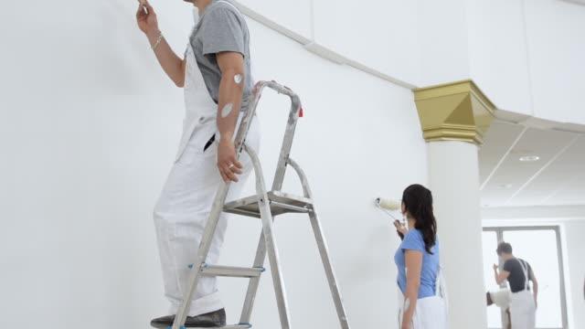MS TU Man and woman painting wall / London, England, United Kingdom
