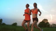 SLO MO TS Man and woman running at sunset
