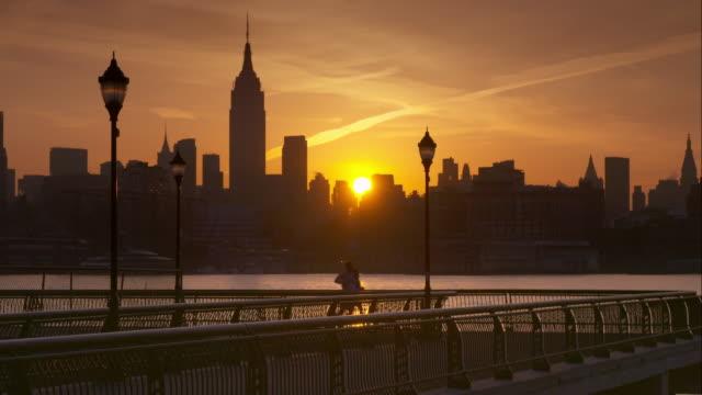 A Man and Woman Running on Pier Overlooking Manhattan