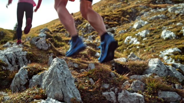 Man and woman running up a rocky meadow high in the mountains in sunshine