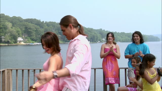 Man and woman salsa dancing on rooftop overlooking lake at party as people watch in background / New Jersey