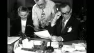 Man and woman seated at a desk are handed a piece of paper by another in a loud tie