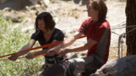 A man and woman setting up a slackline between two trees in the wilderness.