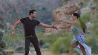 SLO MO. Man and woman share elegant dance in mysterious natural setting.