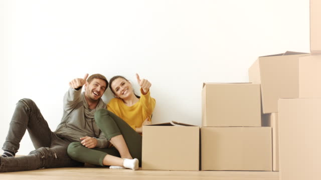 Man and woman showing thumbs up in room full of cardboard boxes