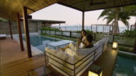WS Man and woman sitting on poolside patio sofa overlooking hotel suite, with sea in background / Hua Hin, Thailand