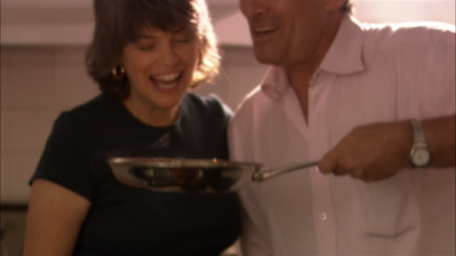 Man and woman smelling cooked food in pan and kissing each other on lips