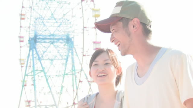 Man and woman smiling with Ferris wheel in background