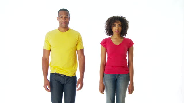 man and woman standing side by side looking at camera
