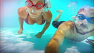 Man and woman swim underwater slowmotion