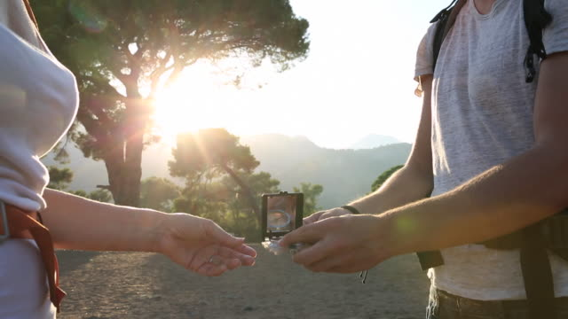 Man and woman take compass reading on hike through woods