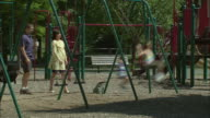 WS Man and woman talking as they push their children on the public park swing set/ Fanwood, New Jersey